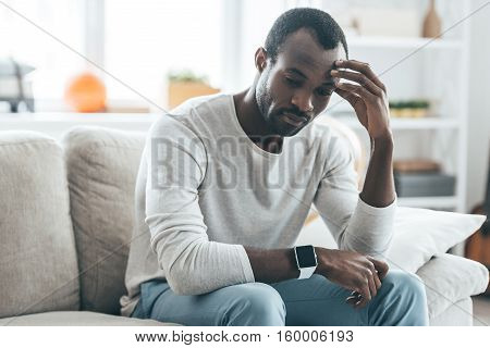 Many things to think about. Handsome young African man touching head with hand and looking uncertain while sitting on the sofa at home