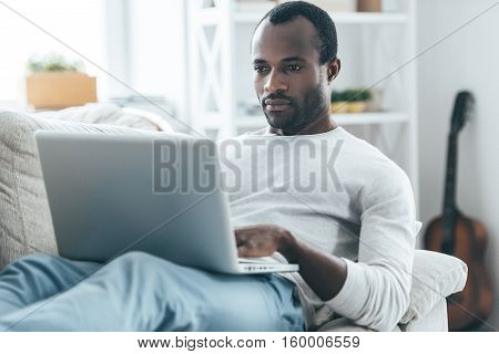 Focusing on something. Handsome young African man looking at laptop with serious face while lying on the sofa at home