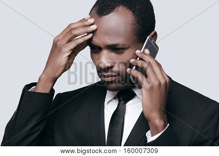 Bad news! Handsome young African man touching head with hand and talking on the phone while standing against grey background