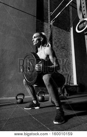 Heavy weight. Good looking sporty young woman holding barbell weight and squatting while having weight training