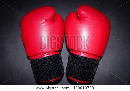 The red boxing gloves on the black background