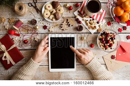 Christmas composition. Hands of unrecognizable man holding tablet. Various objects laid on table. Studio shot, wooden background. Copy space.