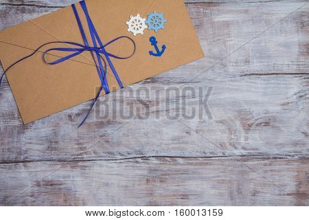 Kraft Envelope In Marine Style With Blue Ribbon, Anchor And Steering Wheel