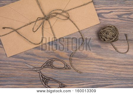 Konevert Tied With Twine And Scissors On A Wooden Table