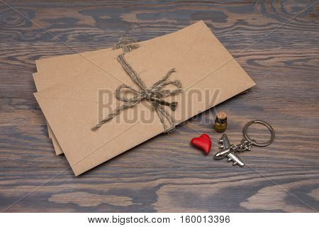 Stack Of Envelopes And Souvenirs From Travels On Wooden Background