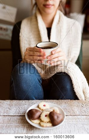 Unrecognizable woman with white knitted scarf holding a mug with coffee. Jam cookies and gingerbread laid on old wooden table.