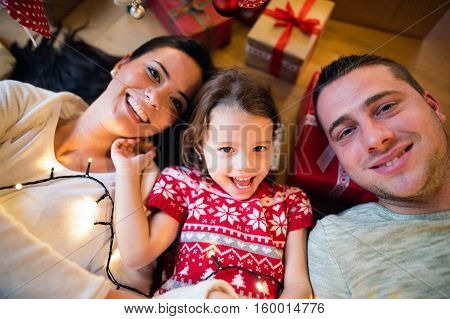 Young parents with their little daughter under Christmas tree lying among presents.