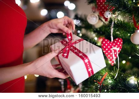 Hands of unrecognizable young woman in front of illuminated Christmas tree inside in her house unwrapping present. Close up.