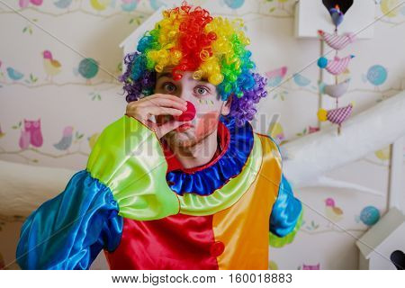 Clown pushes himself on the nose.
