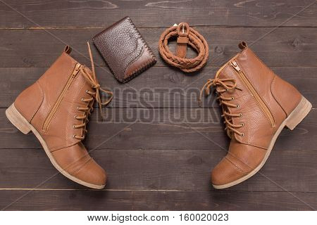 Brown Wallet, Brown Boots And Brown Leather Belt On The Wooden Background