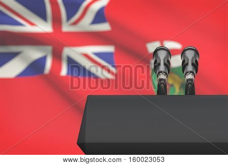 Pulpit And Two Microphones With Canadian Province Flag On Background - Manitoba