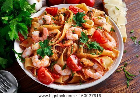 Tasty Pappardelle pasta with shrimp, Squid, mussel, tomatoes and herbs