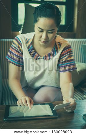 Trendy weekend lifestyle. Woman using tablet pc for online shopping and another hand holding credit card while sitting on a couch. Shopping at home concept with vintage filter effect