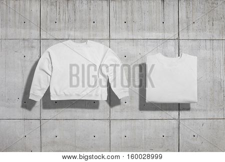 Plain white cotton short sweatshirt folded and unfolded front view on industrial concrete background