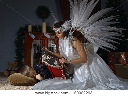 White Angel And Sleeping Boy Near Christmas Tree