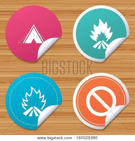 Round stickers or website banners. Tourist camping tent icon. Fire flame and stop prohibition sign symbols. Circle badges with bended corner. Vector