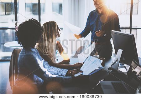 Young team of coworkers making great meeting discussion in modern coworking office.Hispanic businessman talking with two beautiful womans.Teamwork process.Horizontal, blurred background, sun effect