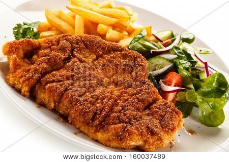 Fried pork chop, French fries and vegetables isolated on white background