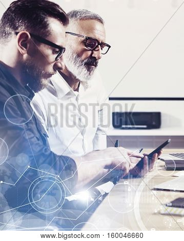 Concept of digital screen, virtual connection icon, diagram, graph interfaces.Bearded young man holding mobile phone and touching display.Adult businessman working together with partner.Vertical