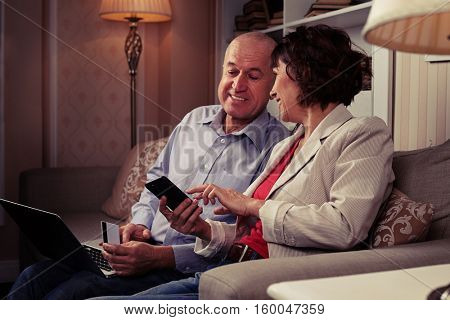 A mid shot of a smiling pair looking at something funny on the phone. People sitting on the settee with cute cushions, a laptop on man'?s knees