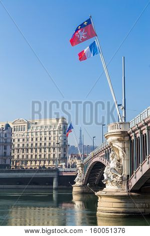 A bridge over a river with city buildings at the other side and a french flag flying