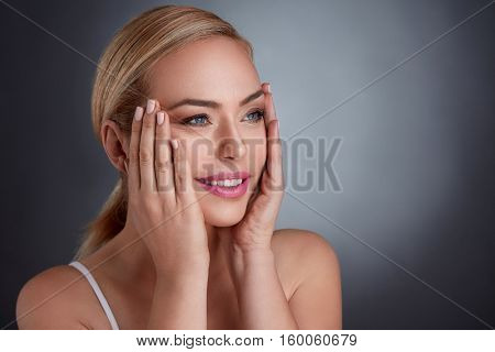 middle age woman tightening skin on face with hand, make you look younger