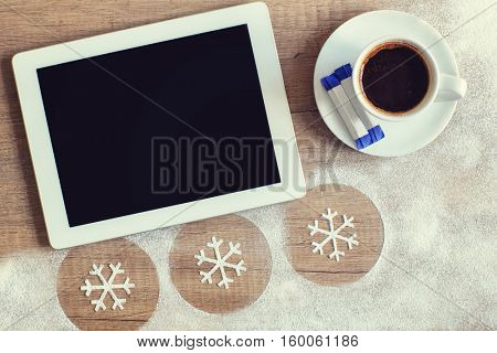 Tablet and mug of coffee with sugar on wooden background