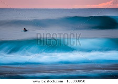 Surfer in the ocean among the waves. Completely motion blurred image