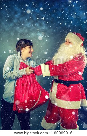 Santa Claus takes a bag with gifts from the teenager.