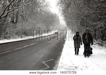 London, UK - Jan 20, 2013 : A family enjoying a winter stroll in a heavy fall of snow along the side of  Wandsworth Common