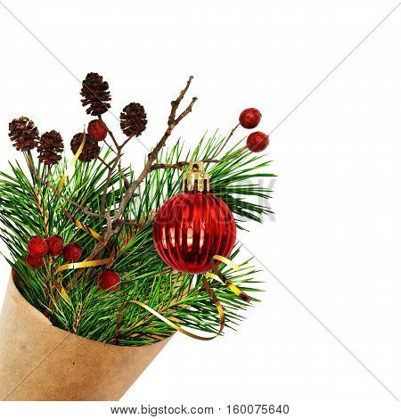 Christmas bouquet with pine twigs cones berries and red ball in a craft paper cornet isolated on white