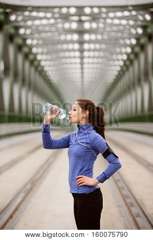 Beautiful young woman with smart phone and earphones, listening music, running in the city on green steel bridge, resting, drinking water from bottle.
