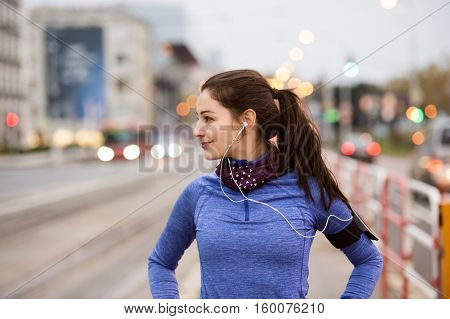 Beautiful young woman with smart phone and earphones, listening music, running in the city against road with cars