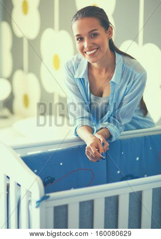 Young smiling woman standing near children's cot