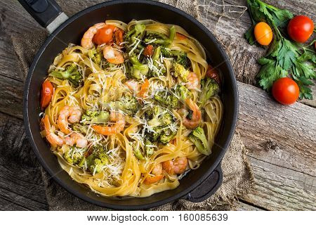 Pasta linguine with shrimps and broccoli in dripping pan on wooden background. Flat lay.