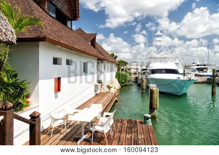 Different yachts in dominican republic on water in bay near the white buildnig with table and chairs at sunny day with clouds on blue sky