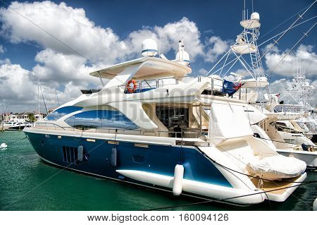 Different yachts in dominican republic on water in bay at sunny day with clouds on blue sky
