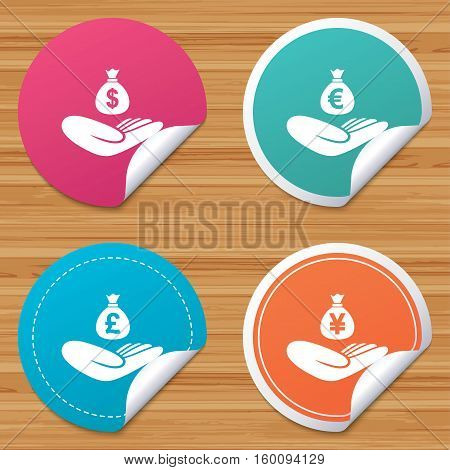 Round stickers or website banners. Helping hands icons. Money insurance symbols. Hand holds cash bag in Dollars, Euro, Pounds and Yen signs. Circle badges with bended corner. Vector