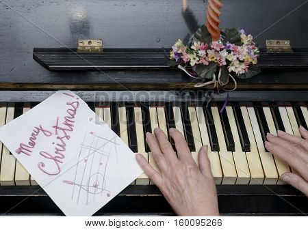 Female hands playing on a retro looking piano Christmas background indoor overhead shot