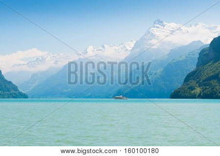 Grandiose mountain landscape. Mountain tops in the snow. Steamship floats on the lake.