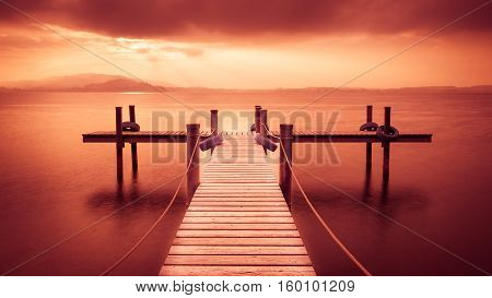 Wooden pier on the lake. Fog. Long exposure. Toning expression red.