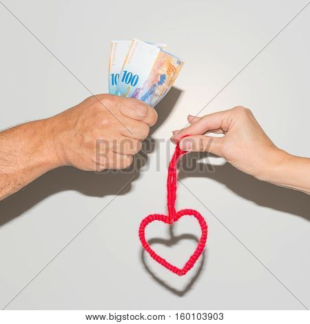 Man's hand with banknotes. Female hand with a heart symbol.