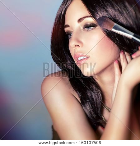 Closeup portrait of a beautiful woman with shiny glossy hair doing makeup over colorful background, applying brush for powder, perfect fashion look