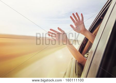 Person's hands out of the car window driving down a country road