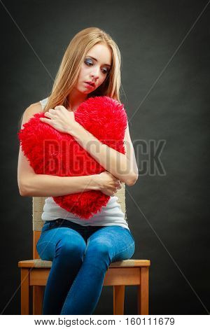 Broken heart love concept. Sad unhappy woman sitting on chair hugging red heart pillow dark background