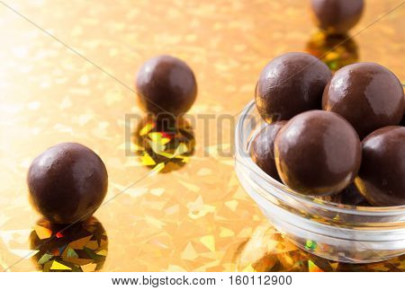 Round Chocolate Candy In Small Glass Cup On Colorful Background