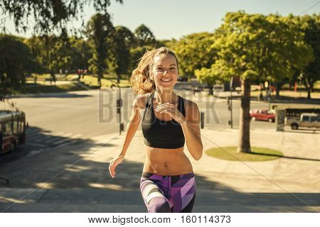 Happy beautiful blonde girl full of energy running training and smiling in sporty clothes in the morning with city and trees on the background. Healthy lifestyle. Sporty woman jogging.