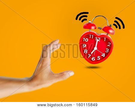 Red bell alarm clock wake up at 7 o'clock with human hand try to stop it.