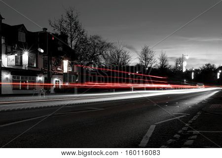 Red and white light trails through a village at twilight