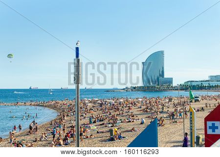 Barcelona, Spain - September 17, 2016; Barcelonetta Beach with architecturally modern W Hotel in distance paraglider above and cargo ships on horizon sunbathers along sandy beach Barcelona Spain